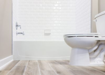 Sparkling clean white bathroom with wood floors after house cleaning service