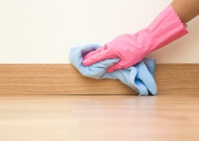 Cleaner with pink glove wiping a baseboard